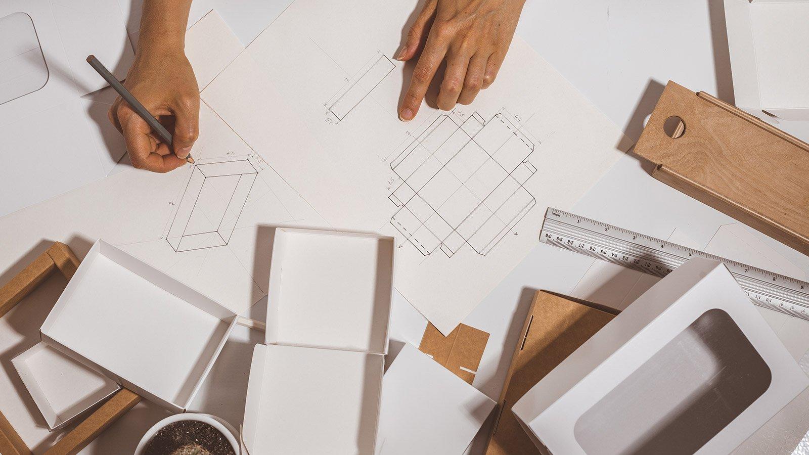 Designer drawing a mockup for economic cardboard box